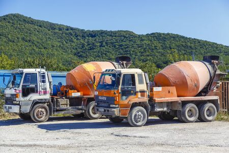 Concrete trucks on the construction site. Cars are not new, the dusty and dented in places.
