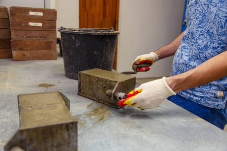 A member of the construction of the laboratory takes a sample of concrete. He loads the concrete into a special mold with a trowel. The result is a cubic concrete blank