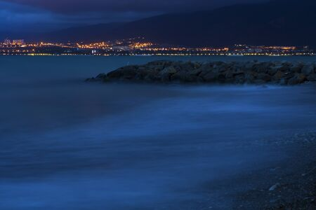 Sea surf on a long exposure in the evening. Waves roll over the pebbly beach and rocks. In the background, mountains and city lights. Long exposure.