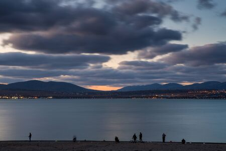 Fishermen on the shore of Gelendzhik Bay stand in a row and catch a Sargan. Blue evening. Long exposure. Clouds. Mountains in the background. Philosophical and sad mood