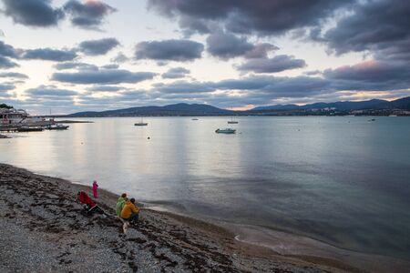 Evening winter beach in Gelendzhik. Blue evening. Long exposure. Clouds. Mountains in the background. Philosophical and thoughtful mood. Contemplation. People sit on the beach and look thoughtfully