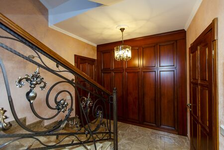 A rich and beautiful staircase with wrought iron railings and a wooden handrail leads to a landing with two wooden doors and a built-in wardrobe. The doors are dark cherry color and look very expensive