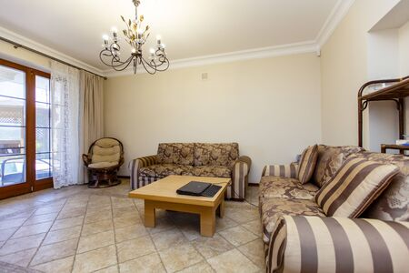 Room in a classic style in beige tones. Two brown-striped sofas. Coffee table with laptop. Beige tiles on the floor. Wrought-iron chandelier, access to the veranda with heavy curtains