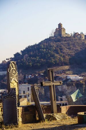 Old crosses and tombstones. In the background on the hill is Tabor Monastery of the Transfiguration. Tbilisi, Georgia. Winter