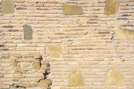 An old brick wall interspersed with large stones of sand and gray colors. The brick is badly destroyed. Background.