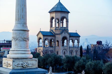 Bell tower at the entrance to the Holy Trinity Cathedral in Tbilisi at sunset.