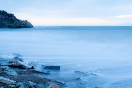 Storm surges at slow shutter speeds on a pebble-sandy beach, the resort of Gelendzhik, the twilight.