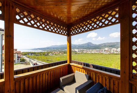 View of the mountains and the sea from a wooden gazebo on the hillside in the cottage village.