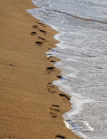 Traces of a man in sneakers on a sandy beach are washed away by an incoming small wave.