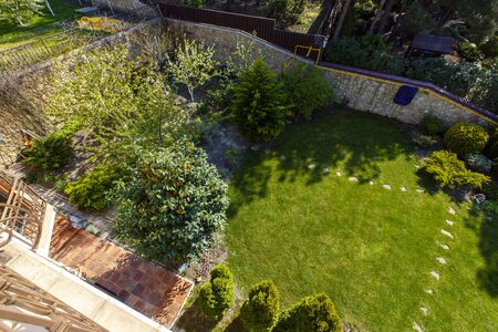 The backyard of a classic cottage in the spring. In front of the cottage is a large green lawn with trimmed grass, flowering trees, paths and paths. Landscape design. Juicy spring grass and leaves Imagens