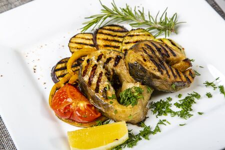 Sturgeon steak with vegetables. Delicious sturgeon steaks are grilled and served on a white square plate with lemon and tomato. Sprinkled with greenery. Close-up side view.