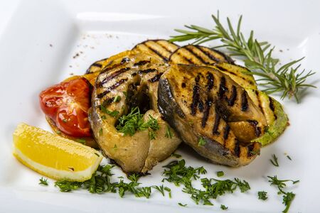 Sturgeon steak with vegetables. Delicious sturgeon steaks are grilled and served on a white square plate with lemon and tomato. Sprinkled with greenery 版權商用圖片