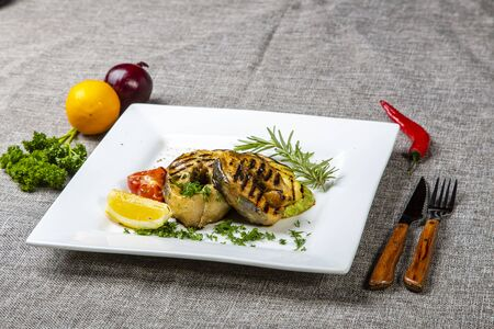 Sturgeon steak with vegetables. Delicious sturgeon steaks are grilled and served on a white square plate with lemon and tomato. The plate is on a gray canvas, next to the onion, lemon, red pepper, knife and fork. The view from the top