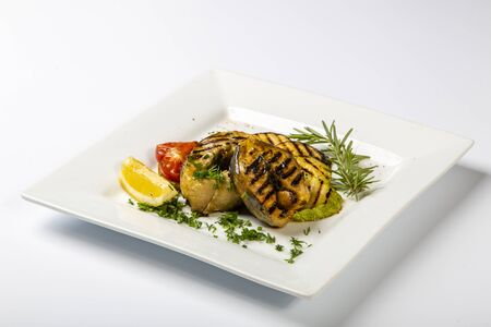 Sturgeon steak on the grill. A few pieces of grilled sturgeon steak lie on a square plate. Sprinkled with herbs, decorated with lemon and tomato