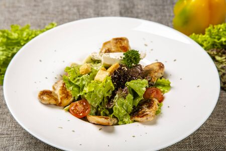 Caesar with chicken and feta cheese.  Served on a round white plate: pieces of fried chicken, cheese, tomatoes, salad. Plate on a gray canvas, decorated with salad, pepper