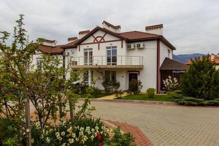 Cottage blanc à deux étages au printemps par temps nuageux. Maison blanche au toit rouge, dalles de pavage, fleurs. Montagnes à l'horizon.