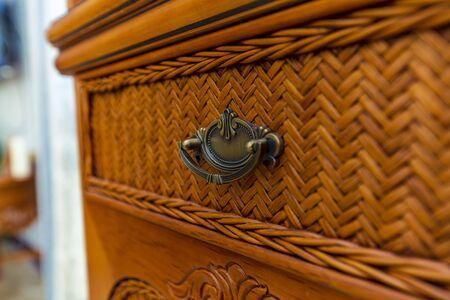 metal vintage vintage handle at the wicker dresser made of wood.