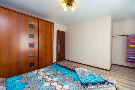 A room in the guest house with a large double bed and a wooden wardrobe. The bed has an azure bedspread with Indian floral motifs.