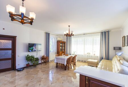 Classic bright living room with wooden furniture in the house. In the center is a table with fruit and four wicker chairs. White large leather sofa. Wardrobe made of wood. Antique Sideboard made of wood. Wooden staircase to the second floor