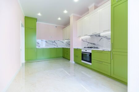 New kitchen set in green and white colors in the style of minimalism in a new building. The top under the marble. The doors in the cabinets are green. Beige walls. Kitchen furniture set with green cabinets.