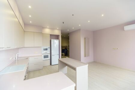 A large room with pink walls and a white kitchen set. Kitchen furniture is new with all kitchen appliances. In front of the kitchen is a white table. Fresh, new renovation..