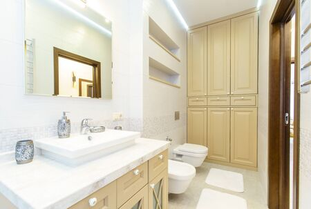 bathroom with elegant rectangular washbasin, toilet and shower. Mirror with light on top. The white tile..