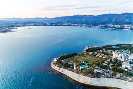 Entrance from a height to the Gelendzhik Bay at sunset in calm, windless weather. In the foreground is a