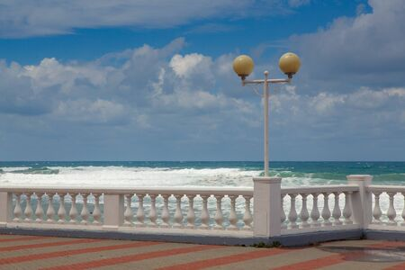 Embankment of the resort city of Gelendzhik. balustrade and lights of the embankment against the background of storm waves. Stock Photo