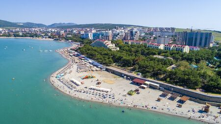 Beach of Gelendzhik resort. Numerous sun umbrellas and sun loungers. Embankment with balustrade. Houses and trees behind the embankment.