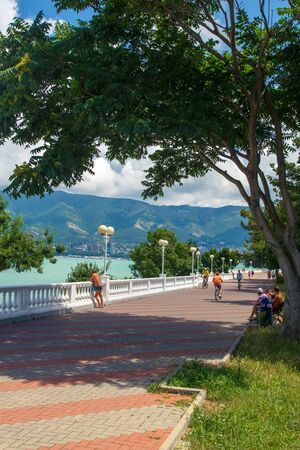 The embankment of the resort of Gelendzhik in clear Sunny weather. White balustrade and street lights. The Caucasus mountains are in the background Archivio Fotografico