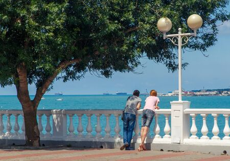A young couple-a man and a woman, stand on the embankment of the resort of Gelendzhik under a green tree and look out to sea. They are leaning on a white balustrade, with a lantern next to them. Yachts and ships are visible in the sea. Sunny weather.