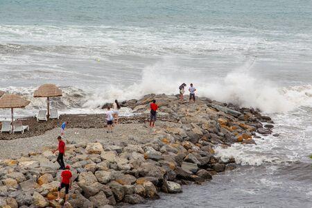 Beach of Gelendzhik resort. Storm waves break on breakwaters made of large rocks. People stand on the breakwaters and look at the waves and spray.