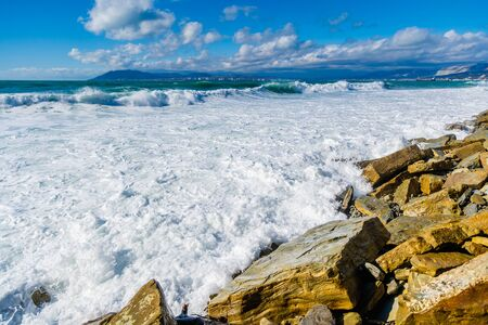 Beautiful white sea foam on the beach during a storm. Waves roll on the shore. There are large yellowish chunks of rock on the shore. Mountains on the horizon. Reklamní fotografie