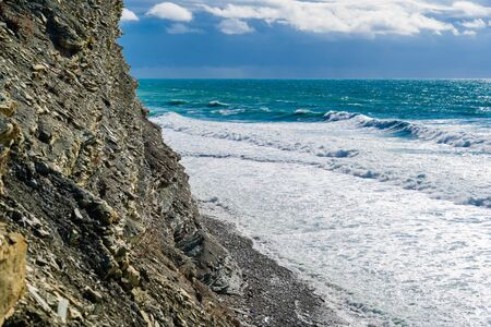 High cliffs and a pebbly beach below. Beautiful storm waves in foam hit the beach