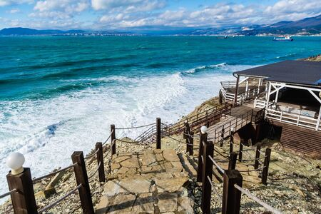 A staircase with stone steps and rope handrails leads down to the green stormy sea. On the horizon mountains and ships on the roadstead of Novorossiysk.