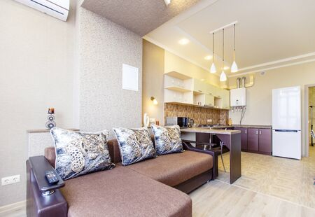 Kitchen in the apartment with a new renovation. A Seating area with a large sofa and TV. The kitchen is in the background