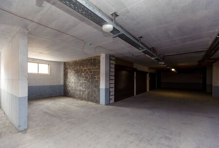 Parking spaces in the basement of an apartment building are separated by walls. some Parking spaces have roller shutters. Stockfoto
