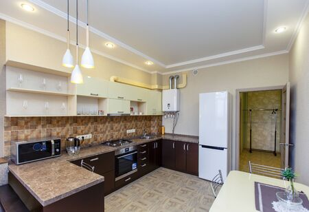 Kitchen in the apartment with a fresh renovation. Kitchen furniture in beige tones, brown tiles. Kitchen appliances: refrigerator, stove, microwave, gas boiler.