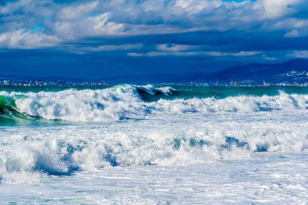 Storm waves in white foam rush in rows along the Tsemesskaya Bay. Blue sky and green sea. Dangerous and dramatic. In the background, mountains, multi-storey buildings of the city and port Foto de archivo