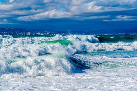 Storm waves in white foam rush in rows along the Tsemesskaya Bay. Blue sky and green sea. Dangerous and dramatic. In the background, mountains, multi-storey buildings of the city and port Standard-Bild