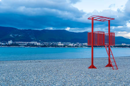 the red lifeguard tower on the pebble beach of the resort town is out of season. No people, empty beach. Winter, clouds. Mountains in the background. High quality photo