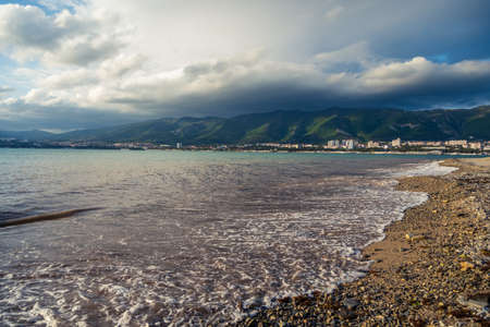 A wave runs over the pebbly beach of the resort town. Sea foam, pebbles. In the background, mountains covered with clouds. City at the foot of the mountains. High quality photo