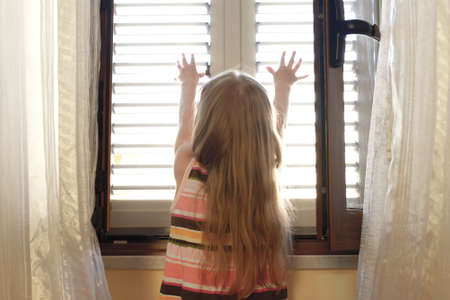jalousie: child at the open window, pushes to open Stock Photo