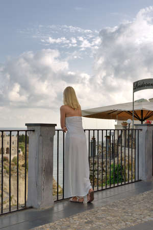 railing: Woman Leaning on Railing, back view Stock Photo