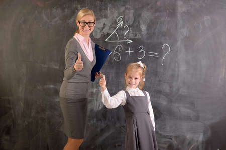 educator: Young teacher and student stand at the blackboard