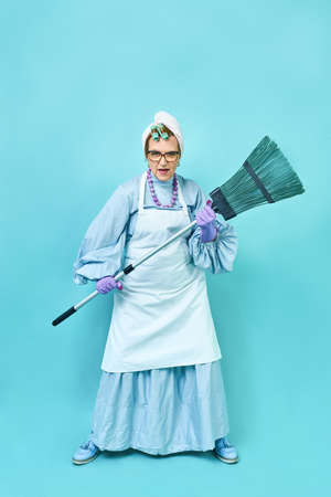 Cleaning Lady Fun. Elderly funny housewife fooling around with a broom. Full body isolated blue