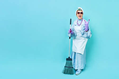 Cleaning Lady Fun. Elderly funky housewife fooling around with a broom. Full body isolated. Фото со стока