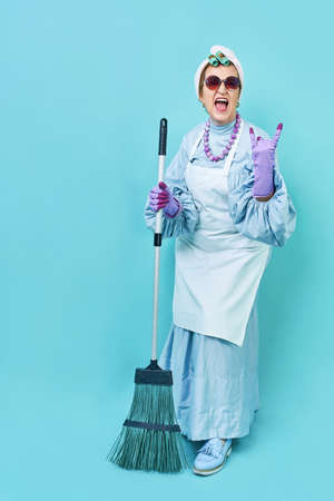 Cleaning Lady Fun. Elderly funky housewife fooling around with a broom. Full body isolated