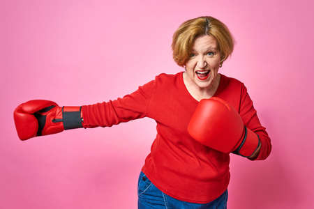 Woman aged in boxing gloves. The concept of the fight against old age.