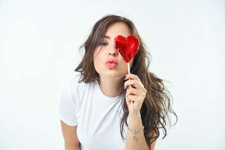 Portrait of a cute girl with a heart shaped lollipop. Woman smiling, looking at the camera, Beautiful white-tooth smile. Separately on a white background. The concept of feelings of affection